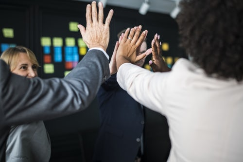 Group of colleagues high fiving one another at a support session for mental health