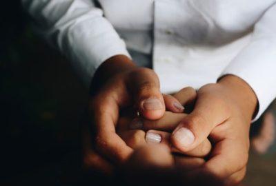 Doctors hands holding patient's hands