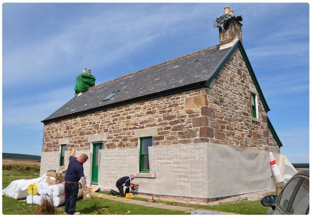 Damp experts stand round a little cottage with tools replacing the damp proof barrier