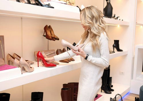 Blonde woman buying fashion shoes in fancy store