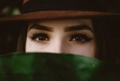 Woman in hat peers over green plant with tightened eyes after non-surgical eye lift