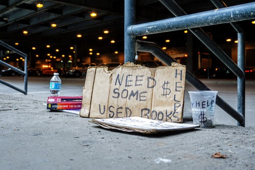 Cardboard street sign asking for used books to give to homeless charity