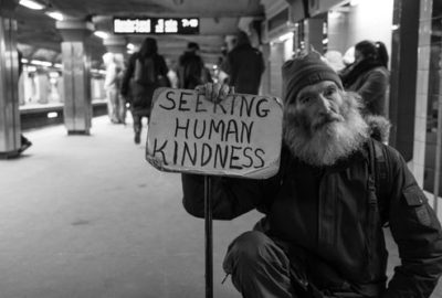 "Homeless man holds up sign reading ""Seeking Human Kindness"" as he begs for charity in the subway station"