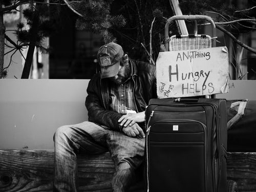 "Homeless Man with Sign reading ""Hungry"" seeks charity from passersby"